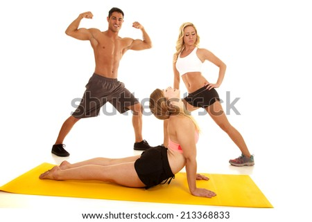 A man with two women stretching out their bodies. - stock photo