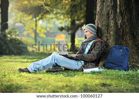 A man working on a laptop in the city park - stock photo