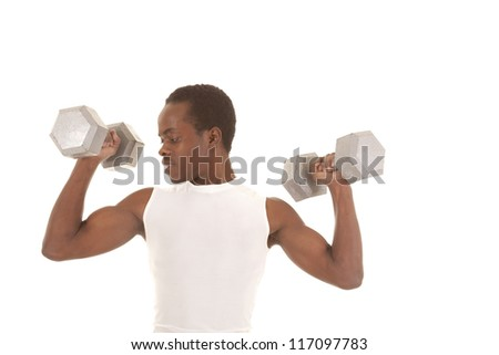 A man working out with big weights doing arm curls looking at his bicep. - stock photo