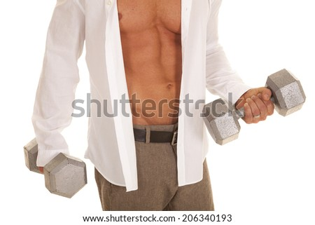 A man working out with weights while still in his business clothes. - stock photo