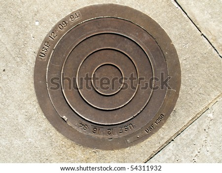 A manhole cover at a rest stop near Greenville, SC. - stock photo