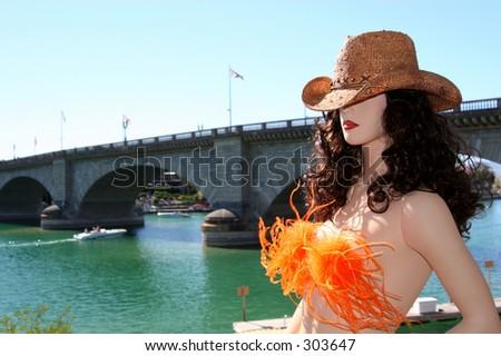 A mannequin with a cowboy hat on overlooks the London Bridge in Lake Havasu City, Arizona. - stock photo