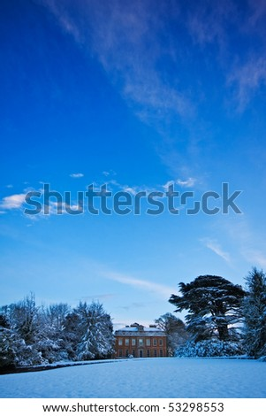 A manor house in a snowy winter landscape, with big blue sky overhead. Copyspace for your text/design. - stock photo