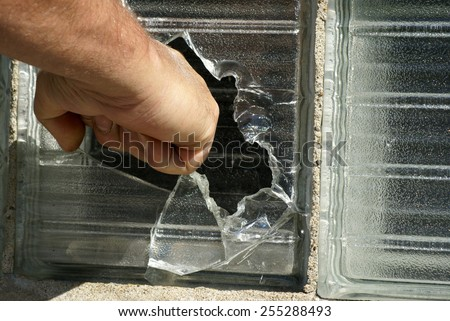 A mans fist breaks threw a glass window. - stock photo