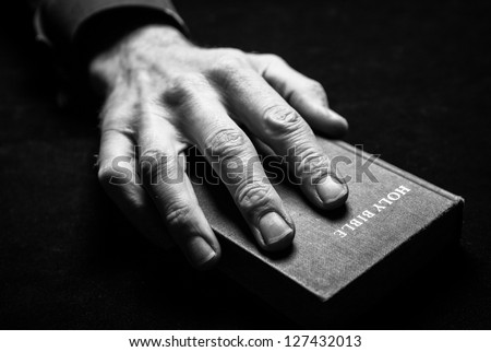 A mans hand holding the Holy Bible. - stock photo