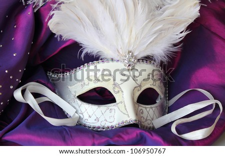 A mardi gras masquerade ball mask on a dress made from purple satin - stock photo