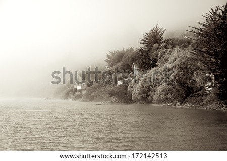 A marine fog slowly rolls in, obscuring homes and forest where the Russian River flows into the Pacific in Northern California. - stock photo