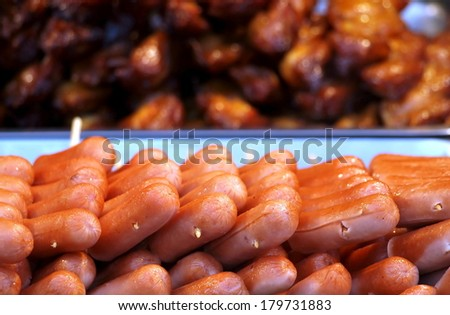 A market stall sells roasted hot dogs and fried chicken pieces  - stock photo