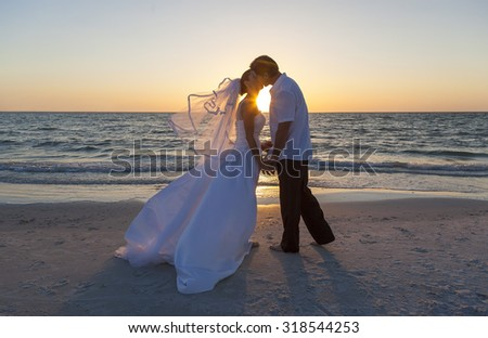A married couple, bride and groom, kissing at sunset or sunrise on a beautiful tropical beach - stock photo