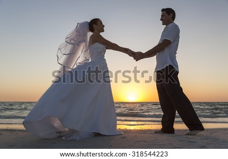 A married couple, bride and groom, sunset sunrise wedding on a beautiful tropical beach - stock photo