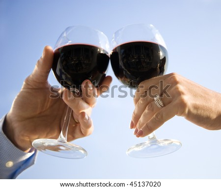 A married couple's hands toasting with red wine. Horizontal shot. - stock photo