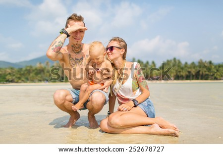 a married couple with a child spend time on the beach - stock photo