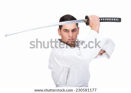 A martial arts man is standing with a sword, isolated on the white background. - stock photo