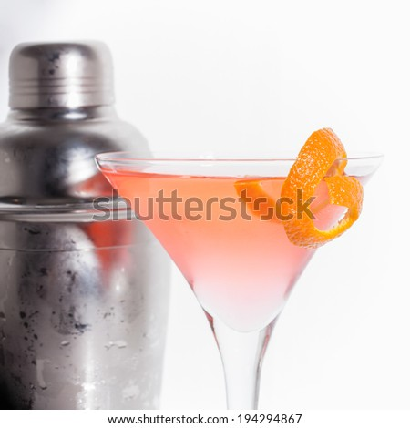 A martini glass is filled with a pink cosmopolitan cocktail with a piece of orange garnish on the rim; square format, white background and surface; a cocktail shaker sits in the background - stock photo