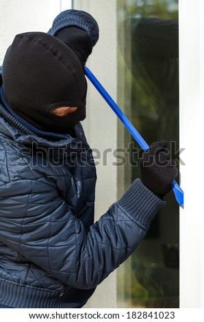 A masked burglar trying to open the window with a plastic stick - stock photo