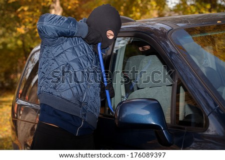 A masked thief striving to steal a big car - stock photo