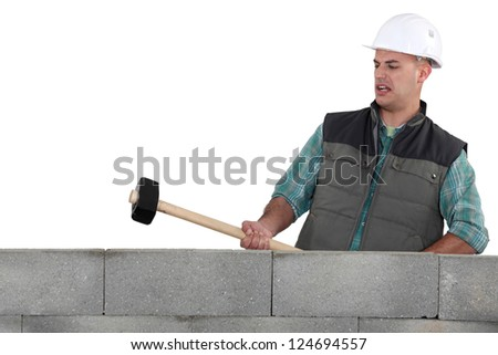 A mason about to destroy a wall with a sledgehammer. - stock photo