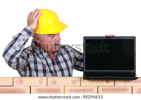 A mason with a laptop. - stock photo