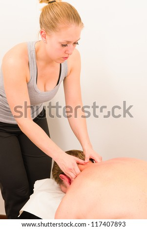 A masseur is massaging a male customer's neck in her surgery - stock photo