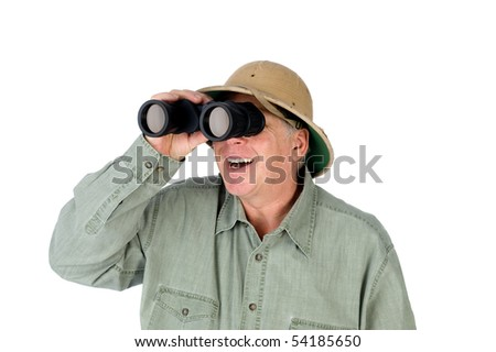 A mature adult man wearing a pith helmet looks through a pair of binoculars. - stock photo