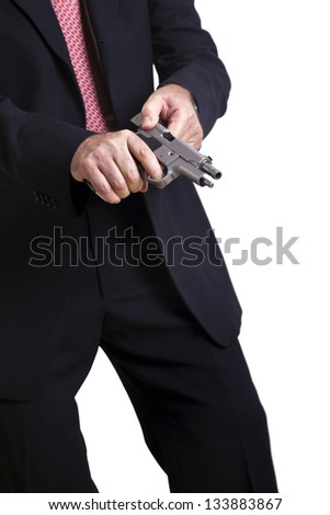 A mature adult man wearing a suit, cocking a 9mm gun and getting ready to use it. Isolated on white background. - stock photo