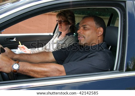a mature African-American man having a driving test and being stressed out by the tester - stock photo