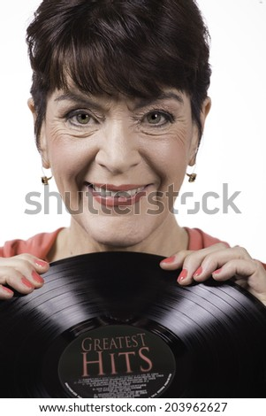 A mature aged woman holds a vinyl music album - stock photo