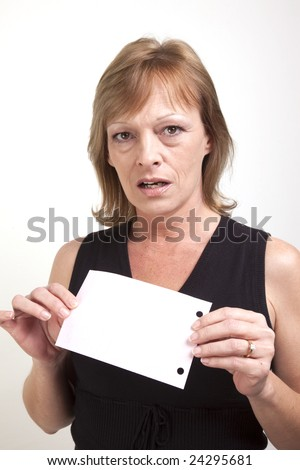 A mature business woman showing surprise while holding up a blank pink slip of paper - stock photo