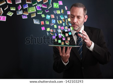 a mature businessman or salesman shows his pad with lots of apps flying around - stock photo