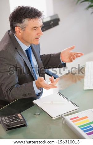 A mature businessman sitting at his desk in an office and explaining something - stock photo