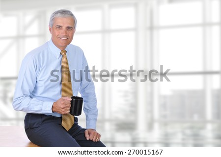 A mature businessman sitting on the corner of his desk in a modern office with a coffee mug in his hand. Horizontal format with copy space.  - stock photo