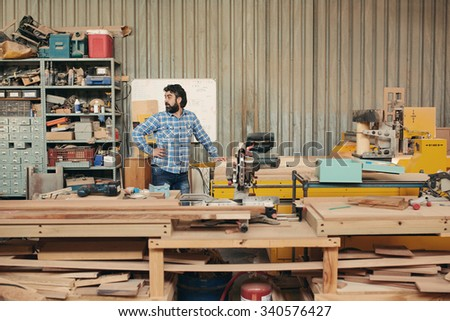A mature carpenter standing behind stacks of planks - stock photo
