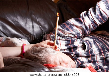 A Mature Male having hopi ear candle treatment - stock photo
