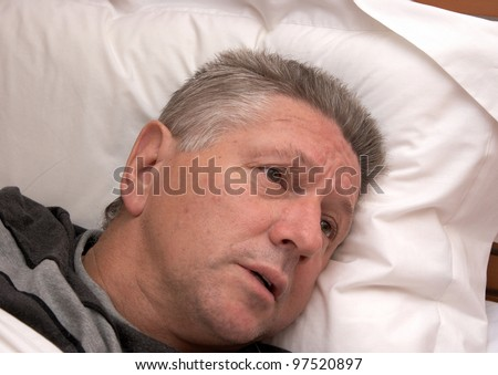 A mature man looking distressed while laying in bed - stock photo