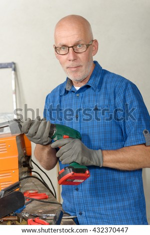 a mature man with a drill in his workshop - stock photo