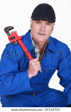 A mature man with a wrench. - stock photo