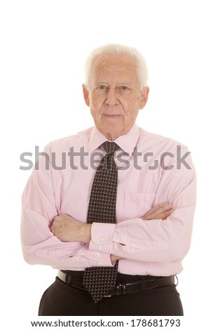 A mature man with his pink shirt on and tie with his arms folded. - stock photo