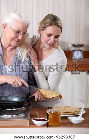 A mature mother and her adult daughter making crepes. - stock photo