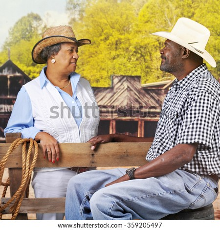 A mature, senior African American couple flirting over a fence in an old western town. - stock photo