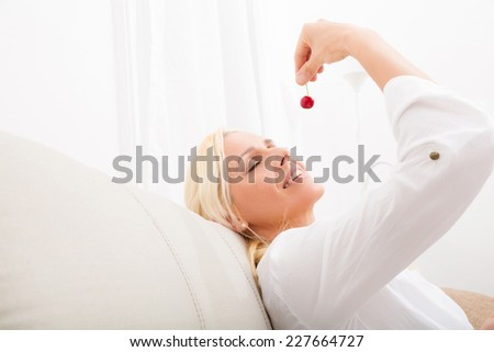 A mature woman enjoying cherries on the sofa.   - stock photo