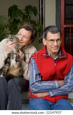 A mature woman lavishing all her attention on her cat, while her husband gets ignored. - stock photo