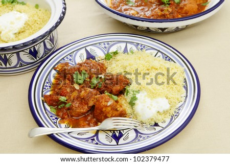 A meal of chicken tagine stew in a spicy, nutty tomato sauce, served with couscous and yoghurt - stock photo