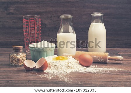 A measuring glass, bottles of milk and other ingredients - stock photo