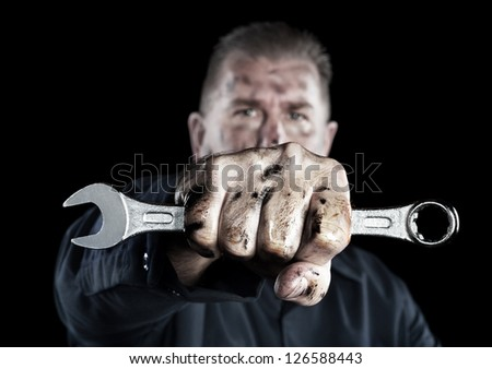 A mechanic covered in grime and grease holds out a box wrench during repairs. - stock photo