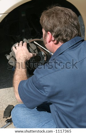 A mechanic inspection the front disc brakes of a car, and preparing to replace the pads. (focus on the wheel & brakes) - stock photo