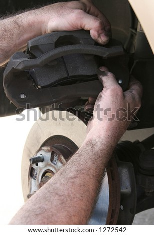 A mechanic's hands inserting new brake pads in the caliper. - stock photo