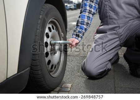 A mechanic solves the nuts of the autowheel to change the tire. - stock photo