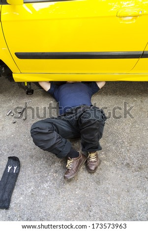 A mechanic underneath a car doing regular maintenance job.  - stock photo