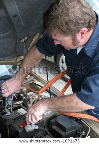 A mechanic using jumper cables to start a car battery.  Vertical. - stock photo