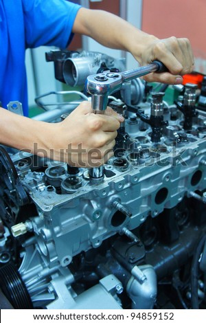 a mechanic working on automotive engine - stock photo